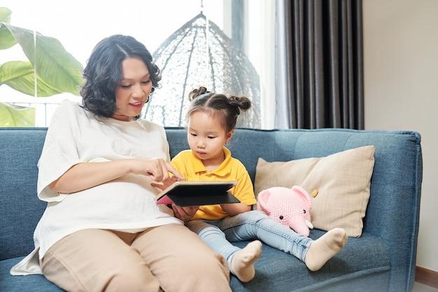 Femme vietnamienne enceinte souriante montrant un nouveau jeu intéressant sur tablette à petite fille