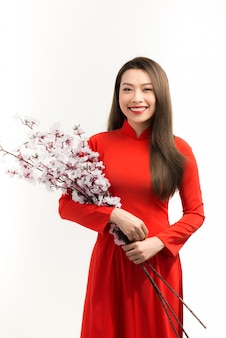 Une femme vietnamienne tenant une fleur signifie une bonne année