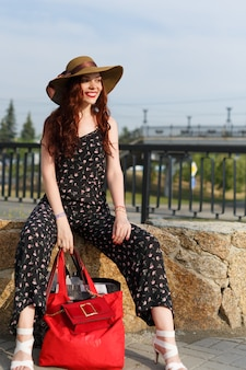 Une femme de la ville se repose avec des colis complets après le shopping.