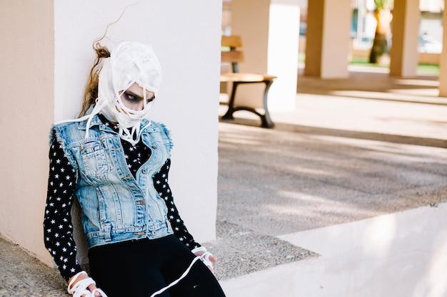 Femme avec visage bandé sur la rue