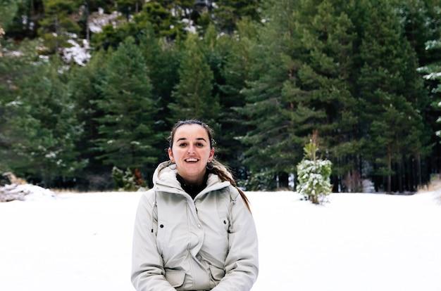 Femme avec un visage heureux assis sur la neige