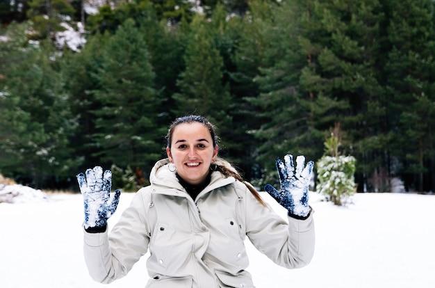 Femme avec un visage heureux exhibant ses gants tachés de neige