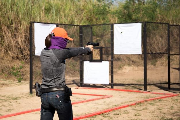 Femme visant le pistolet dans le champ de tir