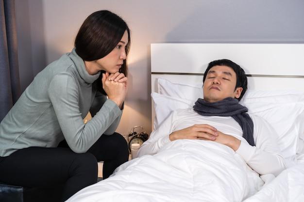 Femme visitant et prenant soin de son mari malade pendant qu'il dort sur le lit à la maison