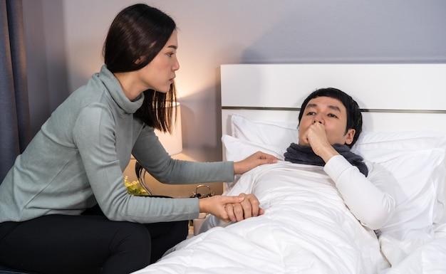 Femme visitant et prenant soin de son mari malade pendant qu'il est allongé sur le lit à la maison