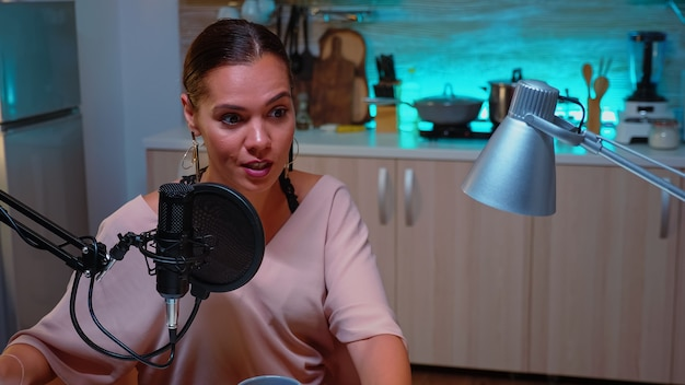 Femme vlogger enregistrant un podcast dans un home studio illuminé par un néon. spectacle en ligne créatif production à l'antenne hôte de diffusion internet en streaming de contenu en direct, enregistrement de médias sociaux numériques