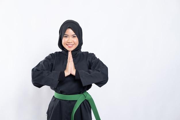 Une femme voilée dans un uniforme de pencak silat pose respectueusement avec ses mains en coupe devant sa poitrine