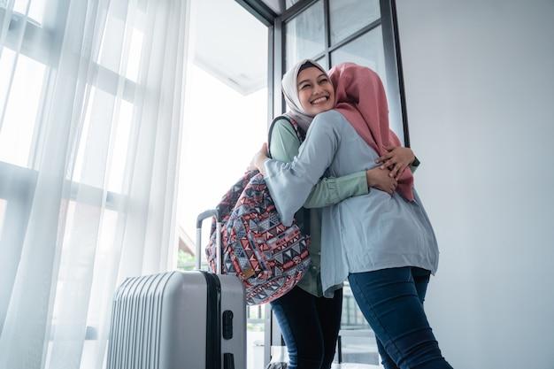 Une femme voilée embrasse sa sœur lorsqu'elle se rencontre à la porte de la maison