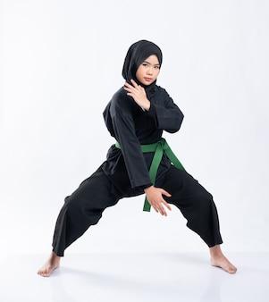 Une femme voilée porte un uniforme de pencak silat avec une ceinture verte avec une position moyenne