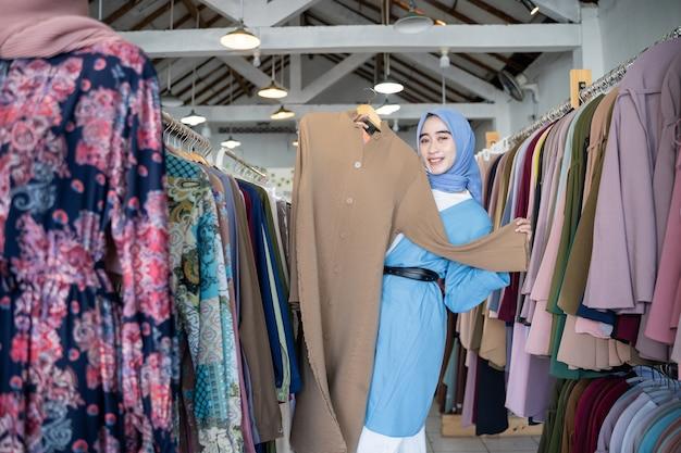 Une femme voilée tient une robe à montrer en se tenant debout