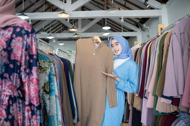 Une femme voilée tient une robe pour montrer et présenter le geste des mains