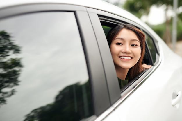 Femme en voiture. belle jeune femme regardant d'une voiture et regardant la caméra