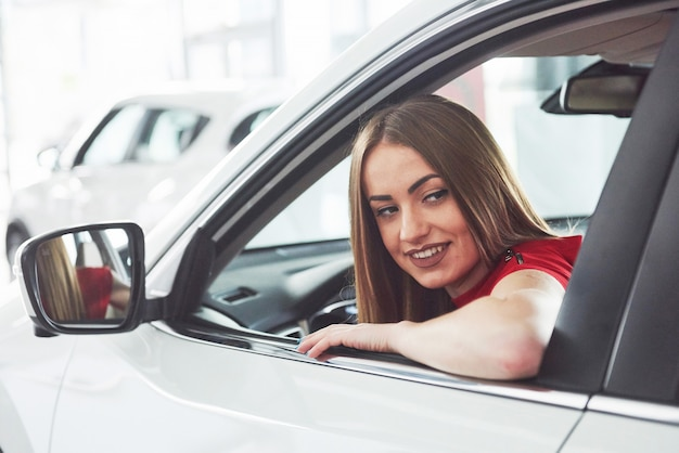 Femme en voiture à l'intérieur garde la roue tournant en souriant en regardant les passagers sur le siège arrière idée chauffeur de taxi contre les rayons du coucher du soleil ciel brillant concept de véhicule d'examen - résidence secondaire la fille