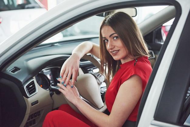 Femme en voiture à l'intérieur garde la roue tournant en souriant en regardant les passagers sur le siège arrière idée chauffeur de taxi contre les rayons du coucher du soleil ciel brillant concept de véhicule d'examen