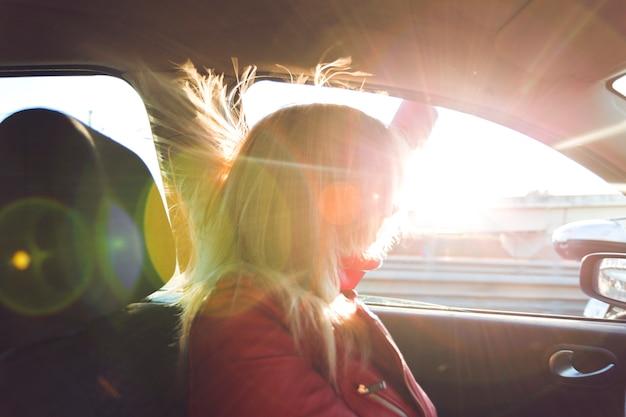 Femme en voiture regardant par la fenêtre