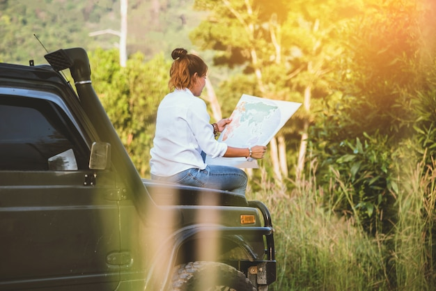 Femme en voiture en voyage avec une carte