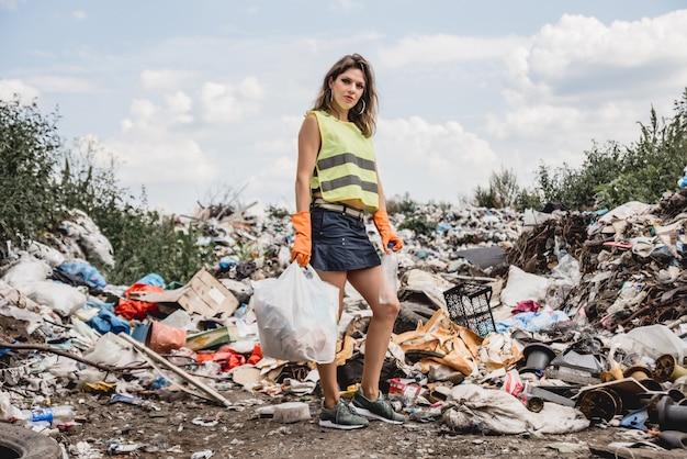 Une femme volontaire aide à nettoyer le champ des déchets plastiques. jour de la terre et écologie.