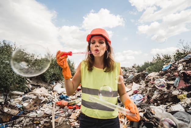 Une femme volontaire avec des bulles aide à nettoyer le champ des ordures en plastique. jour de la terre et écologie.