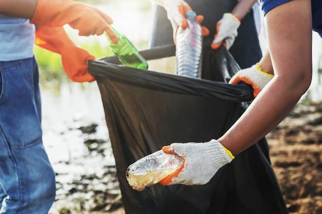 Femme volontaire ramasser des ordures en plastique pour le nettoyage au parc de la rivière
