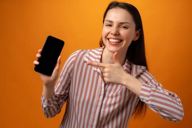 Femme vous montrant l'écran noir du smartphone