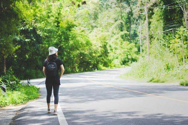 Femme de voyage avec chapeau et sac à dos marchant sur une route à chiangmai