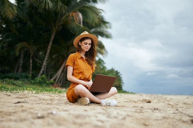 Une femme voyage avec un ordinateur portable le long de l'océan le long du sable avec des palmiers