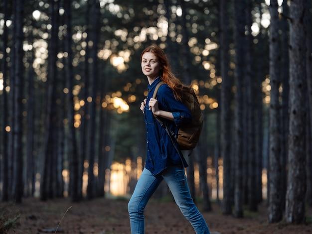Femme voyage parmi les arbres de la forêt en automne et coucher de soleil en arrière-plan