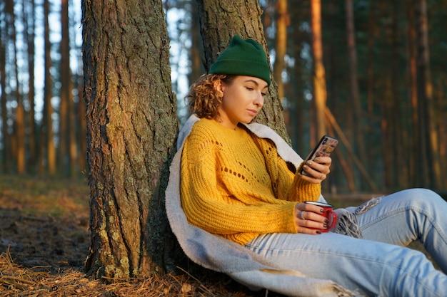 Femme de voyage textos ou lisant ou e-mail dans un smartphone assis détendue avec une tasse de thé sous un arbre