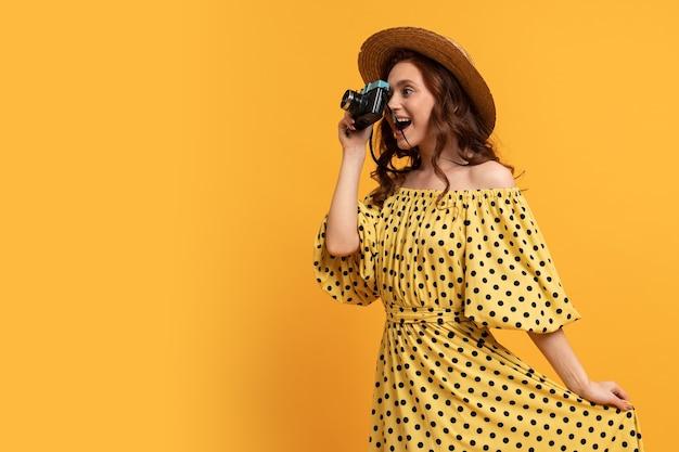 Femme voyageant en chapeau de paille et robe d'été posant avec un appareil photo rétro sur jaune