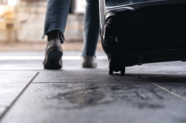 Femme voyageant et traînant un bagage noir à l'extérieur