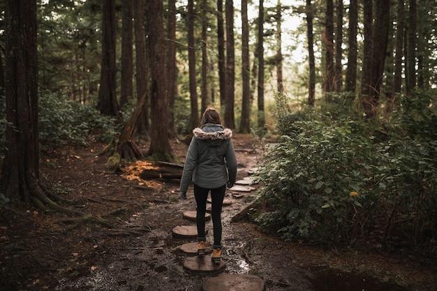 Femme voyageant à travers la forêt