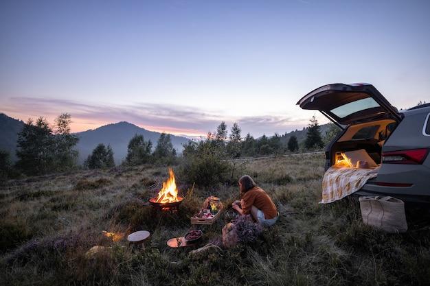 Femme voyageant en voiture et pique-niquant dans les montagnes