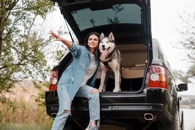 Femme voyageant en voiture avec son chien husky