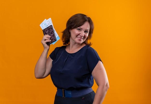 Femme de voyageur d'âge moyen souriant tenant des billets et un portefeuille sur un mur orange isolé avec espace de copie