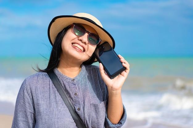 Femme de voyageur à l'aide de smartphone sur la plage