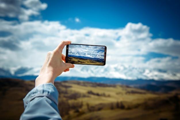 Femme voyageur sur l'arrière-plan d'une chaîne de montagnes enneigée prend des photos sur un téléphone mobile