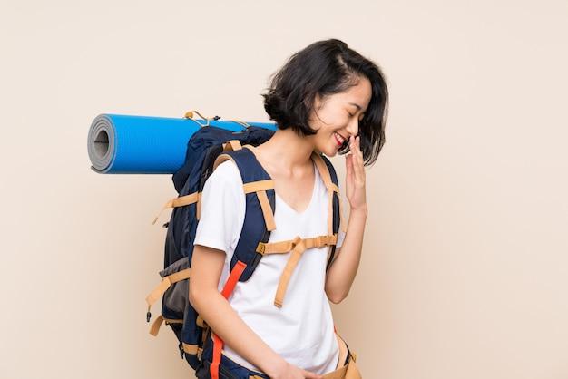 Femme voyageur asiatique sur mur isolé souriant beaucoup