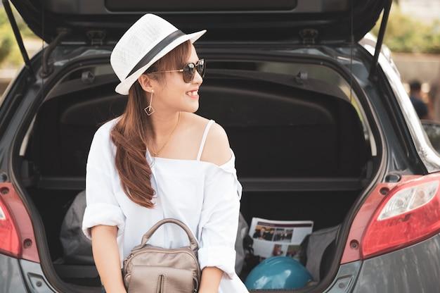 Femme voyageur assis sur une voiture à hayon