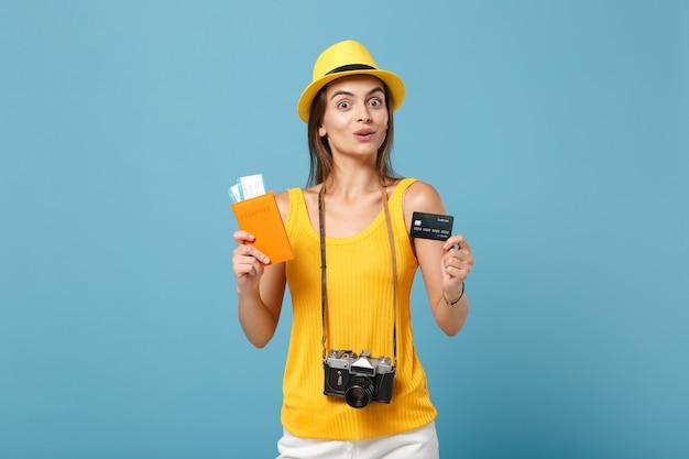 Femme de voyageur en chapeau de vêtements jaunes tenant un appareil photo de carte de crédit de billets sur bleu
