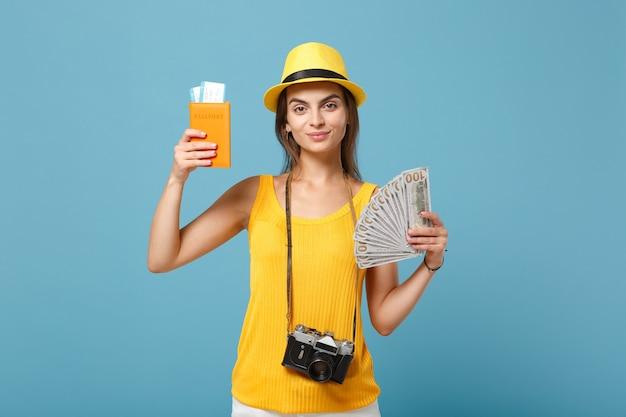 Femme de voyageur dans des vêtements décontractés jaunes et un chapeau tenant une caméra d'argent de billets sur bleu
