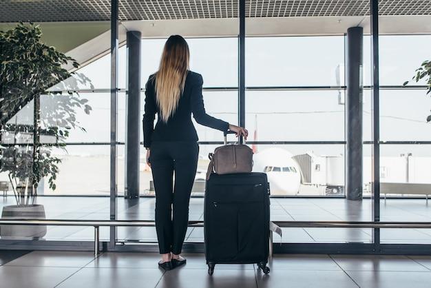 Femme, voyageur, debout, aéroport, terminal, tenue, lourd, valises, regarder, par, fenêtre, avion