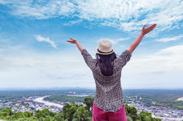 Femme de voyageur étirer les mains avec fond de haute vue