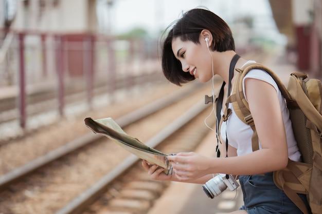 Femme voyageur à former est allé voir les sites touristiques. elle lit la carte