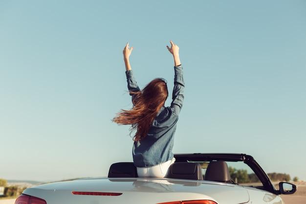 Femme voyageur heureux en voiture cabrio