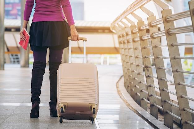 Femme voyageur marchant dans la passerelle de l'aéroport avec sac de voyage.
