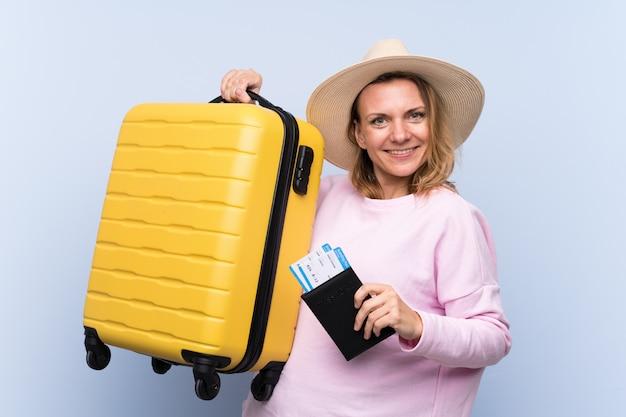 Femme voyageur sur mur bleu isolé