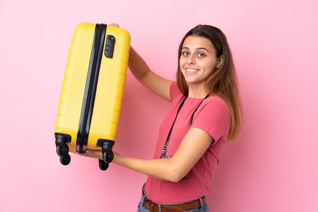 Femme voyageur sur mur rose isolé