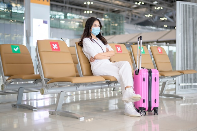 Une femme voyageur porte un masque de protection à l'aéroport international, voyage sous la pandémie de covid-19,