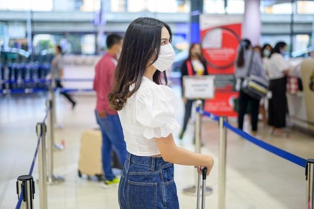 Une femme voyageur porte un masque de protection à l'aéroport international et voyage sous la pandémie de covid-19