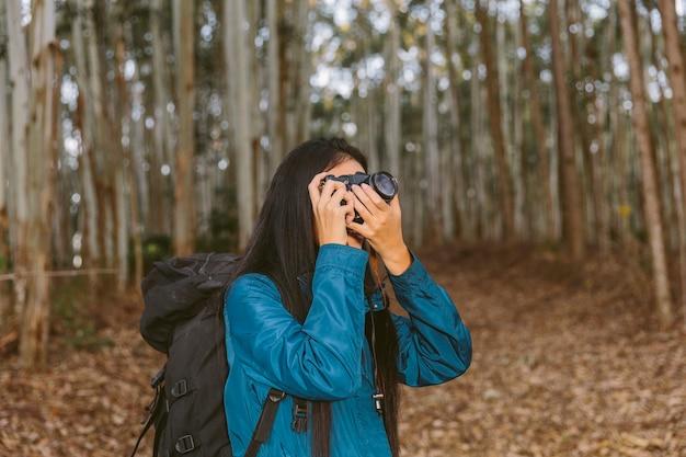 Femme voyageur prenant une photo dans les bois